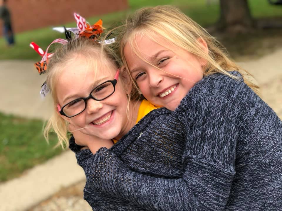Two smiling girls at school